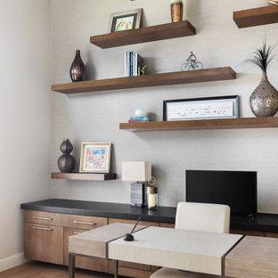 オースティンの広いトランジショナルスタイルのおしゃれなホームオフィス・書斎 (グレーの壁、無垢フローリング、暖炉なし、自立型机、ベージュの床) の写真