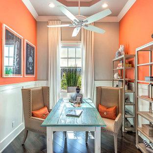 他の地域のビーチスタイルのおしゃれなホームオフィス・書斎 (オレンジの壁、濃色無垢フローリング、自立型机、茶色い床、羽目板の壁) の写真