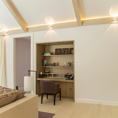 Example of a small trendy built-in desk light wood floor study room design in New York with white walls