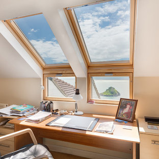 Mid-sized elegant freestanding desk study room photo in Devon with beige walls