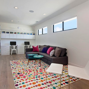 This is an example of a large contemporary study room in Orange County with white walls, light hardwood floors, no fireplace and a built-in desk.