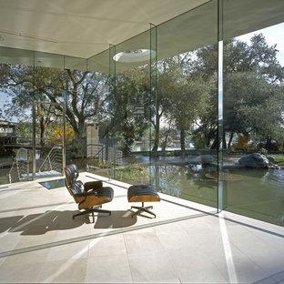 Immagine di un grande ufficio moderno con pareti bianche, pavimento in pietra calcarea, nessun camino e scrivania incassata