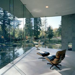 Réalisation d'un grand bureau minimaliste avec un mur blanc, un sol en calcaire, aucune cheminée et un bureau intégré.