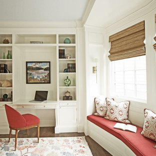 Home office library - mid-sized traditional built-in desk dark wood floor and brown floor home office library idea in Charleston with white walls