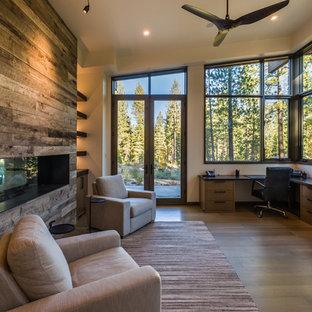 サクラメントの広いコンテンポラリースタイルのおしゃれなホームオフィス・書斎 (白い壁、淡色無垢フローリング、横長型暖炉、木材の暖炉まわり、造り付け机、茶色い床) の写真