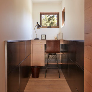 Photo of a small contemporary study in San Francisco with white walls, medium hardwood flooring, a built-in desk and brown floors.