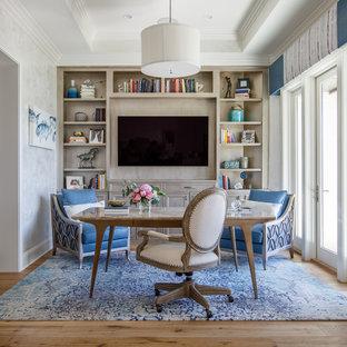 ジャクソンビルの中サイズのビーチスタイルのおしゃれなホームオフィス・仕事部屋 (ライブラリー、暖炉なし、自立型机、白い壁、無垢フローリング) の写真