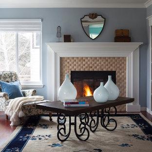 На фото: кабинет среднего размера в современном стиле с библиотекой, синими стенами, темным паркетным полом, стандартным камином, фасадом камина из плитки, отдельно стоящим рабочим столом и коричневым полом