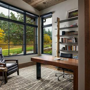 Mittelgroßes Uriges Arbeitszimmer mit Arbeitsplatz, roter Wandfarbe, braunem Holzboden, freistehendem Schreibtisch und braunem Boden in Denver