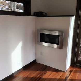 Diseño de estudio minimalista, de tamaño medio, con paredes beige, suelo de madera en tonos medios, chimeneas suspendidas, marco de chimenea de metal y escritorio empotrado