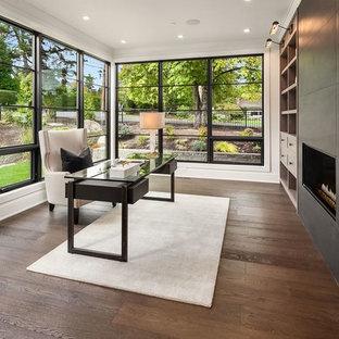 シアトルのトランジショナルスタイルのおしゃれなホームオフィス・書斎 (白い壁、無垢フローリング、横長型暖炉、自立型机、茶色い床、タイルの暖炉まわり) の写真