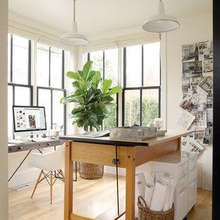 Immagine di un piccolo atelier minimalista con pareti bianche, parquet chiaro, nessun camino, scrivania autoportante e pavimento beige