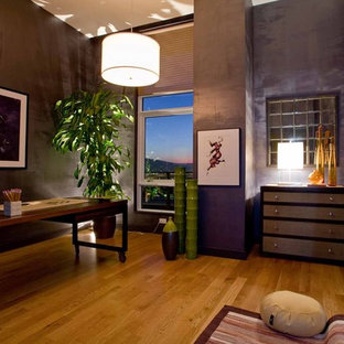 This is an example of a medium sized contemporary home office and library in Portland with purple walls, medium hardwood flooring, no fireplace and a freestanding desk.