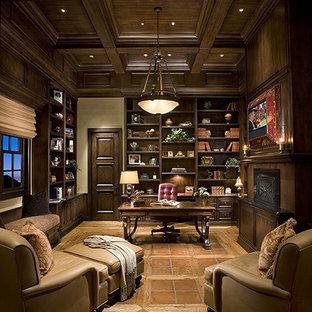 フェニックスの地中海スタイルのおしゃれなホームオフィス・書斎 (ライブラリー、ベージュの壁、テラコッタタイルの床、自立型机、オレンジの床) の写真
