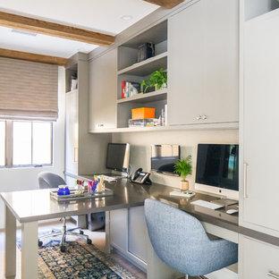 Großes Mediterranes Arbeitszimmer mit weißer Wandfarbe, braunem Holzboden, Einbau-Schreibtisch und braunem Boden in Orange County