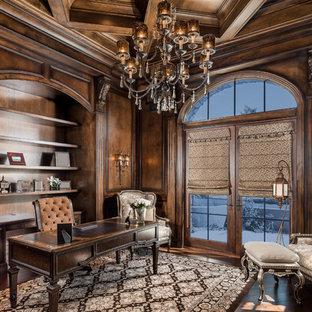 Ejemplo de despacho mediterráneo, grande, con paredes marrones, marco de chimenea de piedra, escritorio independiente, suelo de madera en tonos medios, chimenea de esquina y suelo marrón