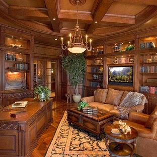 Пример оригинального дизайна: кабинет в средиземноморском стиле с библиотекой, коричневыми стенами, паркетным полом среднего тона и отдельно стоящим рабочим столом без камина