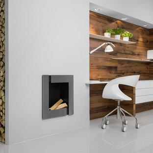 シャーロットの広いミッドセンチュリースタイルのおしゃれな書斎 (造り付け机、白い壁、標準型暖炉、金属の暖炉まわり) の写真