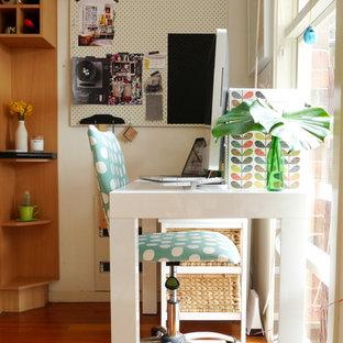 Inspiration för ett eklektiskt hemmabibliotek, med vita väggar, mellanmörkt trägolv och ett fristående skrivbord