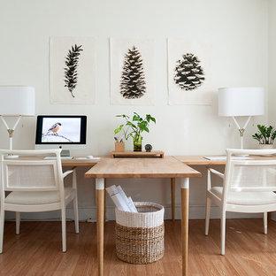 Imagen de despacho clásico renovado, de tamaño medio, con paredes blancas, suelo de madera en tonos medios, escritorio independiente y suelo beige
