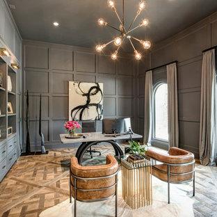 Klassisk inredning av ett arbetsrum, med grå väggar, mellanmörkt trägolv, ett fristående skrivbord och brunt golv