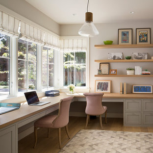 Example of a large cottage built-in desk light wood floor study room design in San Francisco with white walls and no fireplace