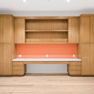 Inspiration för mellanstora moderna hemmabibliotek, med vita väggar, ljust trägolv, ett inbyggt skrivbord och beiget golv
