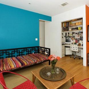 Exempel på ett eklektiskt arbetsrum, med blå väggar, mellanmörkt trägolv och ett inbyggt skrivbord
