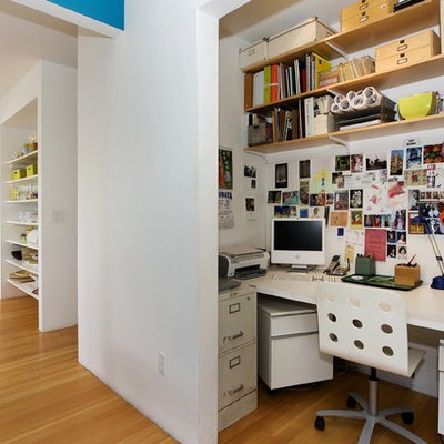 Trendy built-in desk medium tone wood floor home office photo in San Francisco with white walls