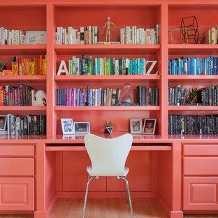Diseño de despacho actual con paredes rosas, suelo de madera clara y escritorio empotrado