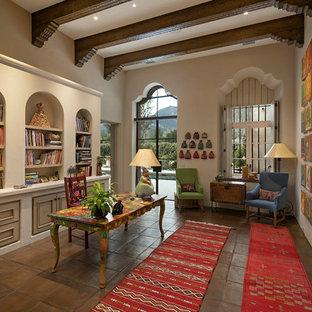 Стильный дизайн: рабочее место в средиземноморском стиле с бежевыми стенами, полом из терракотовой плитки и отдельно стоящим рабочим столом без камина - последний тренд