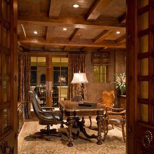 Bild på ett mycket stort amerikanskt hemmabibliotek, med bruna väggar, mellanmörkt trägolv, en öppen hörnspis, en spiselkrans i tegelsten och ett fristående skrivbord