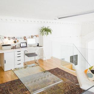 Новый формат декора квартиры: маленькая домашняя мастерская в скандинавском стиле с белыми стенами, паркетным полом среднего тона и встроенным рабочим столом без камина