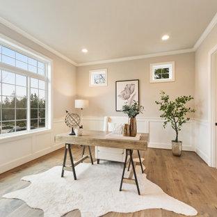Klassisches Arbeitszimmer mit beiger Wandfarbe, braunem Holzboden, freistehendem Schreibtisch, braunem Boden und vertäfelten Wänden in Seattle