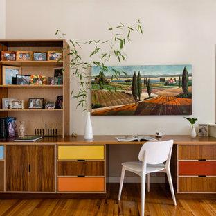 На фото: маленький кабинет в стиле ретро с бежевыми стенами, паркетным полом среднего тона, встроенным рабочим столом и коричневым полом