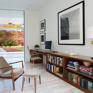 1950s built-in desk light wood floor home office photo in New York with white walls and no fireplace