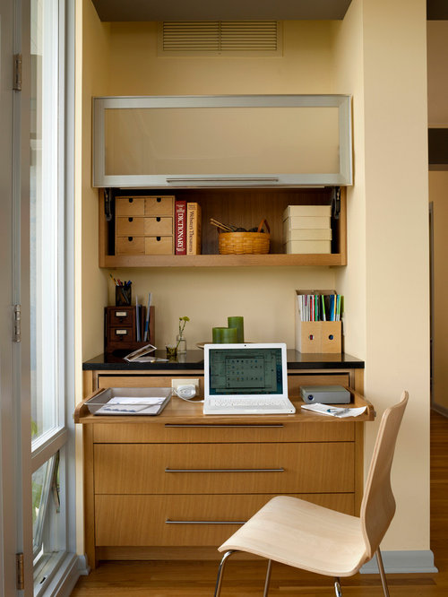 mid sized midcentury modern home office photo in seattle with a built in desk