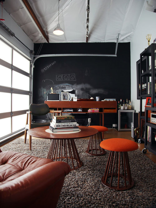 Home office - industrial home office idea in Los Angeles with black walls