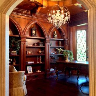Foto di un ampio studio tradizionale con libreria, pareti marroni, parquet scuro, scrivania autoportante e pavimento marrone