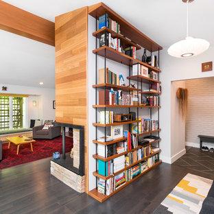 Foto de despacho vintage, grande, con paredes blancas, suelo de madera oscura, marco de chimenea de ladrillo, suelo marrón y chimenea de doble cara