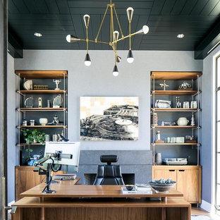 Идея дизайна: рабочее место в стиле ретро с серыми стенами и отдельно стоящим рабочим столом без камина