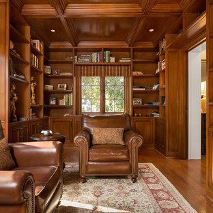 Esempio di uno studio chic con libreria, pareti marroni, pavimento in legno massello medio, camino ad angolo e cornice del camino in pietra