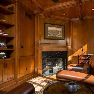 ロサンゼルスのトラディショナルスタイルのおしゃれなホームオフィス・書斎 (コーナー設置型暖炉、ライブラリー、無垢フローリング、石材の暖炉まわり) の写真