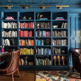 Bild på ett vintage arbetsrum, med ett bibliotek, blå väggar, mörkt trägolv och ett fristående skrivbord