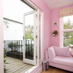 На фото: маленькое рабочее место в современном стиле с розовыми стенами, светлым паркетным полом и отдельно стоящим рабочим столом с