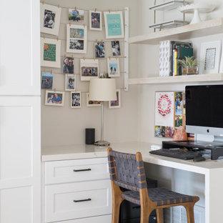 Inspiration för små klassiska hemmabibliotek, med vita väggar, laminatgolv, ett inbyggt skrivbord och brunt golv