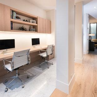 Cette image montre un bureau design de taille moyenne avec un mur blanc, un bureau intégré et un sol blanc.