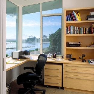 サンタバーバラの中サイズのビーチスタイルのおしゃれなホームオフィス・書斎 (造り付け机、白い壁、コンクリートの床、暖炉なし) の写真