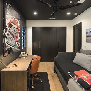 Ejemplo de despacho negro, actual, con paredes negras, suelo de madera clara, escritorio independiente y suelo beige