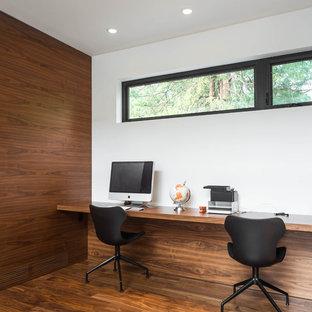 Esempio di un piccolo studio minimalista con pareti bianche, pavimento in legno massello medio, camino classico, cornice del camino piastrellata, scrivania incassata e pavimento marrone